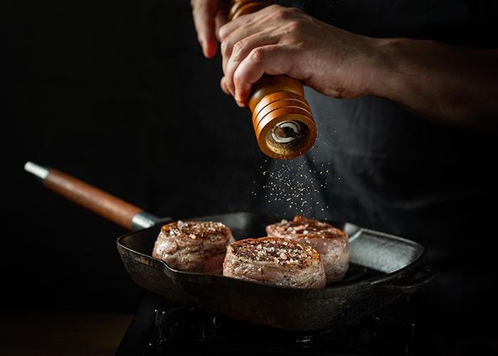dieses Bild zeigt, wie Fleisch mit Knoblauch-Pfeffer gewürzt wird